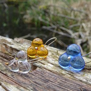 Glasperlen, drei Ohrringe aus Glas in braun, Blau und klar,silber, auf Holz