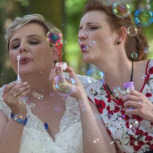 Braut mit blauem Glasschmuck, Frau mit Mohnblumen Kleid und Glasperlenschmuck, Seifenblasen, Hochzeit, Sommer