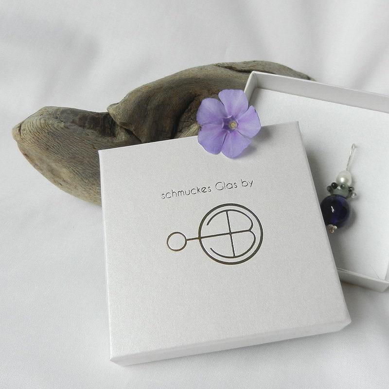 Geschenkschachtel mit silbernem Logo von schmuckes Glas