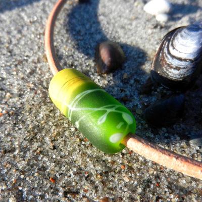 Einzelne Glasperle in Walzenform, handgefertigtes Unikat von schmuckes Glas. Glasperle in zwei Grün-tönen. Hellbraunes Lederband.